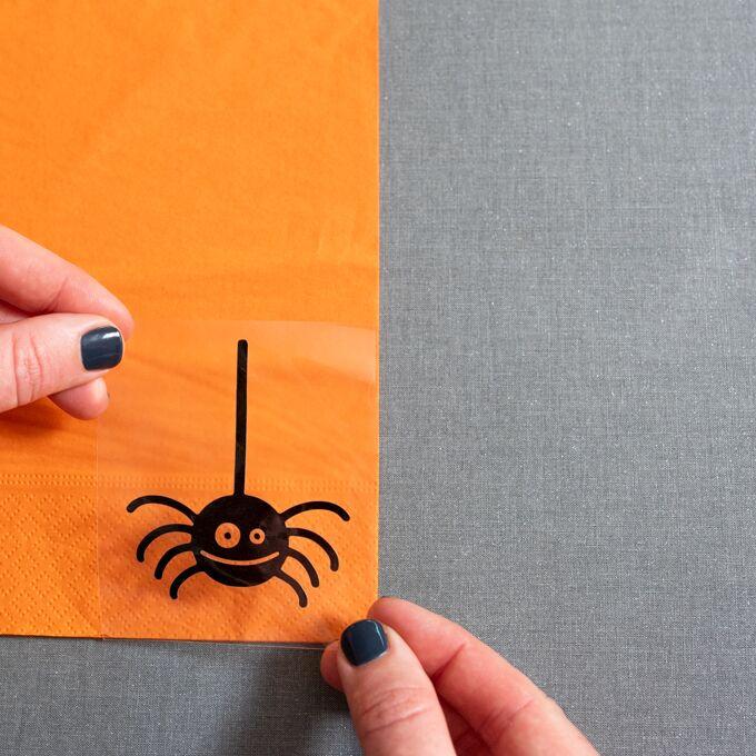 add iron-on spider image onto napkin