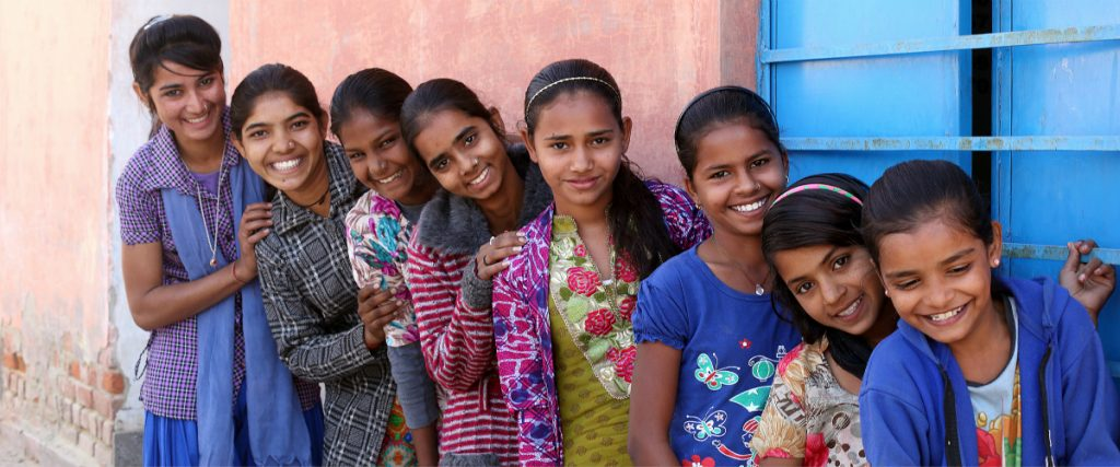 young adolescent girls pose for a group photograph at the AGG meeting at the Anganwadi Centre