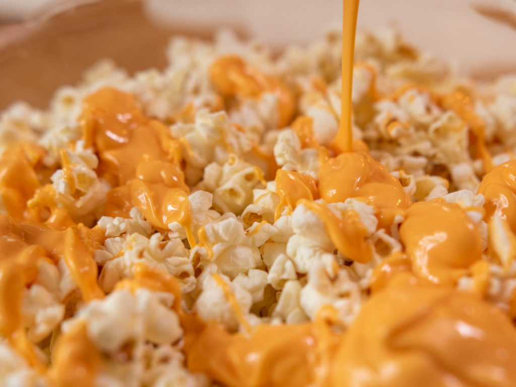 popcorn with drizzle of NESTLÉ® TOLL HOUSE Pumpkin Spice Morsels
