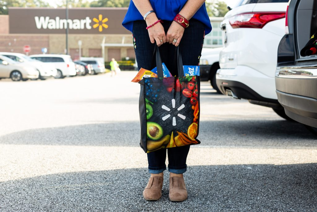 woman holding walmart bag outside of walmart