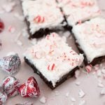 A close up of a brownie with icing and peppermint