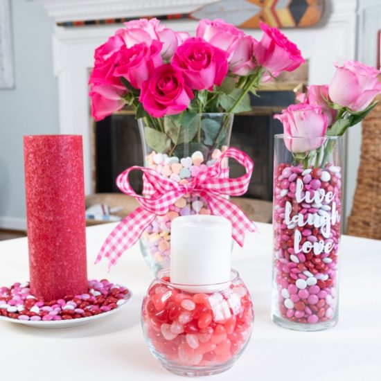 A vase of flowers on a table surrounded by valentine themed home decor