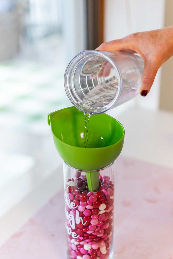 water being poured in vase for m&ms inside large vase for valentine's day candy craft