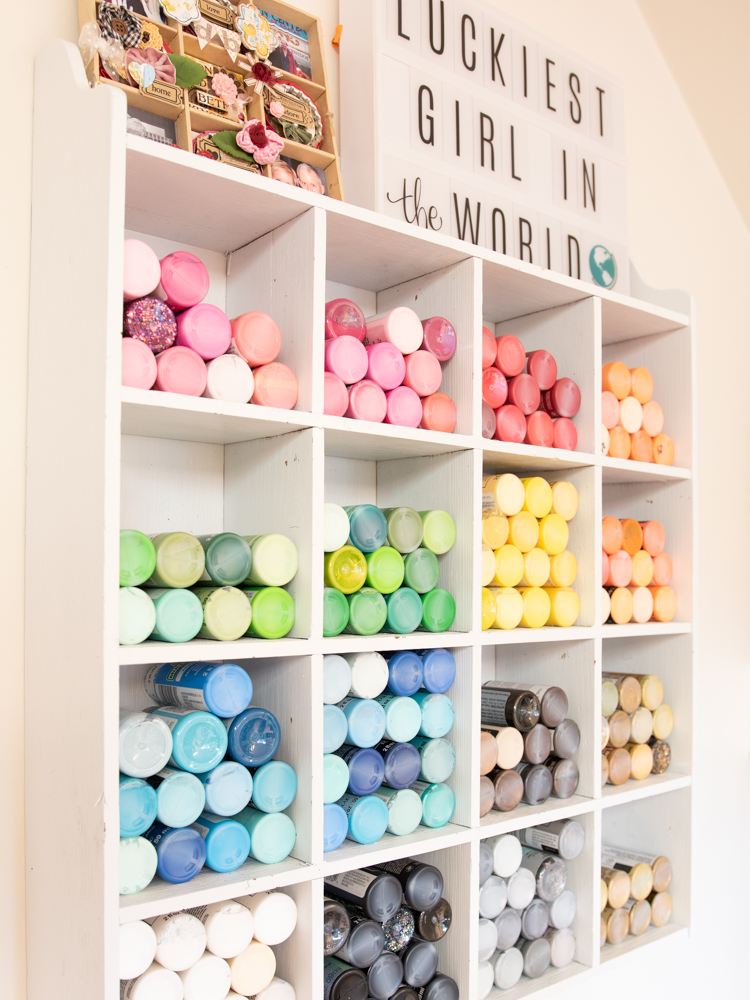 white cube storage shelving with colorful bottles of acrylic paint