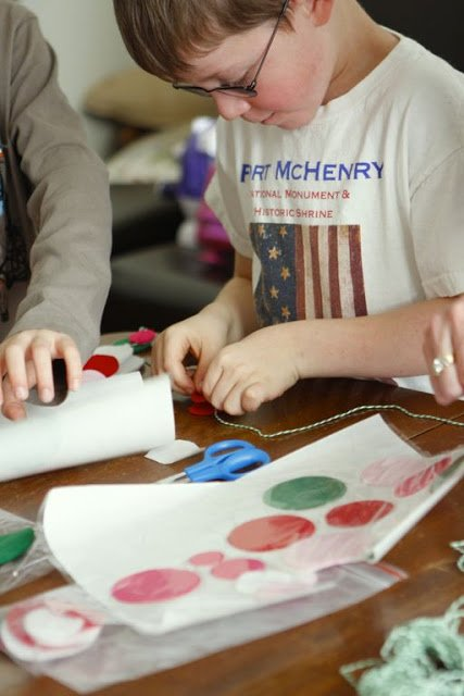 A young boy making a garland out of felt circles
