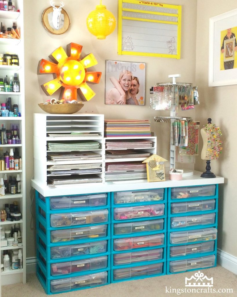 a set of teal plastic drawers filled with craft supplies