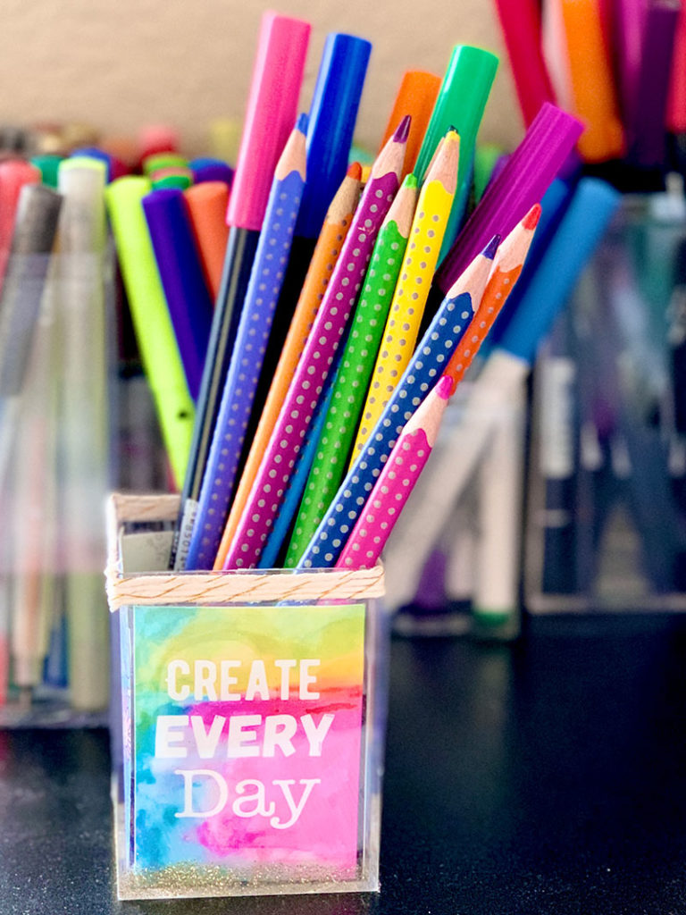 a colorful cup with pencils in it