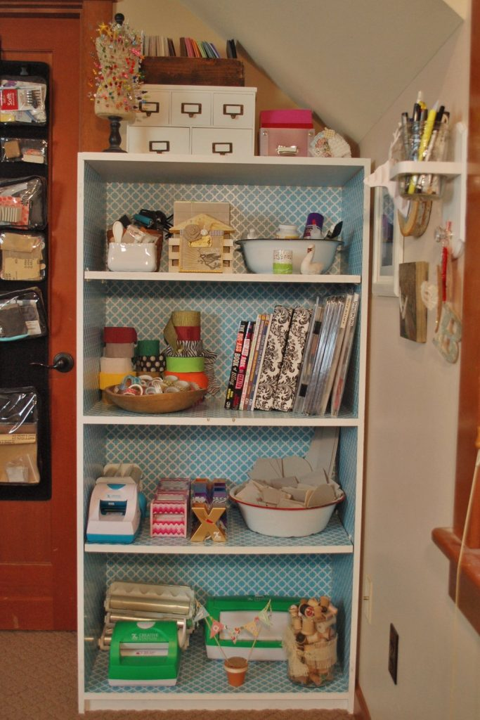 a set of shelves with bowls filled with craft supplies
