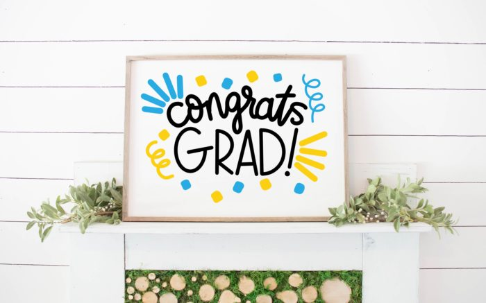 white sign in a wood frame that says congrats grad