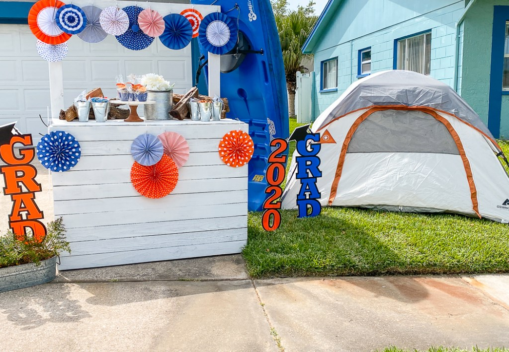 front yard with blue and red rosettes covering a white bar with snacks on it