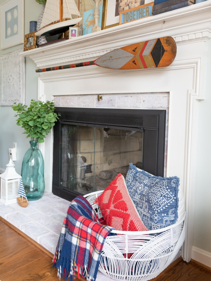 A fireplace with a basket of pillows on one side and a vase on the other