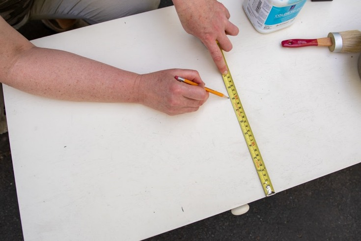 woman drawing line with measuring tape on coffee table