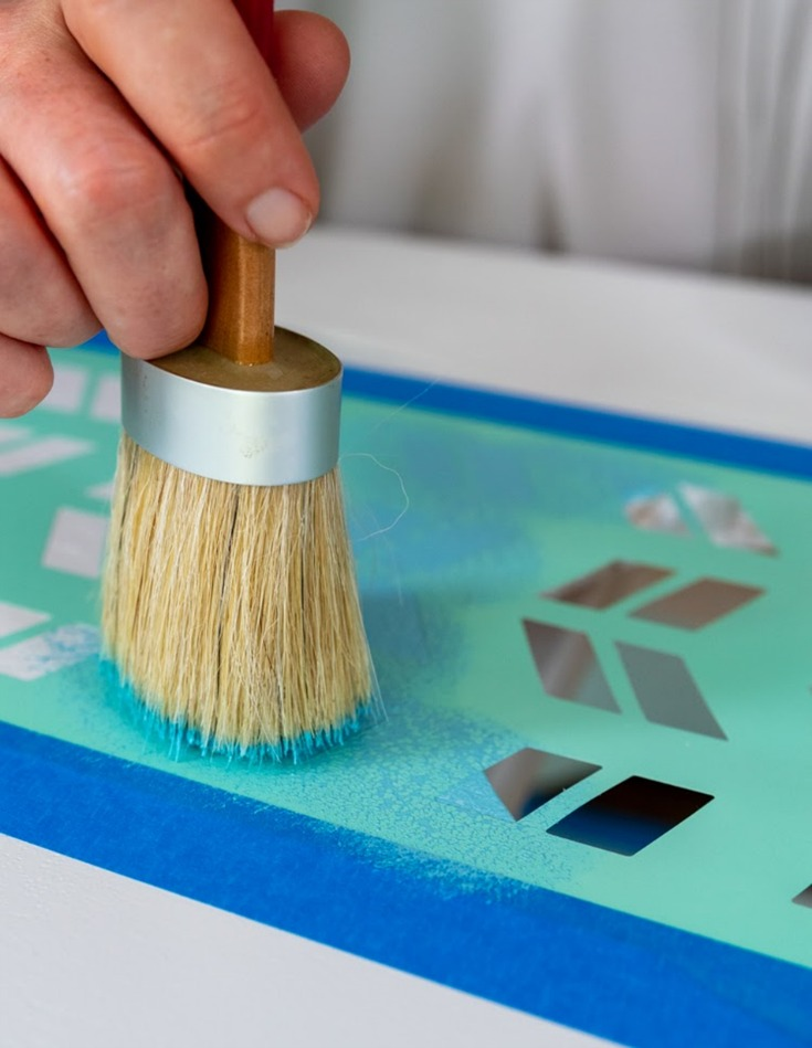 woman painting coffee table using brush and stencil