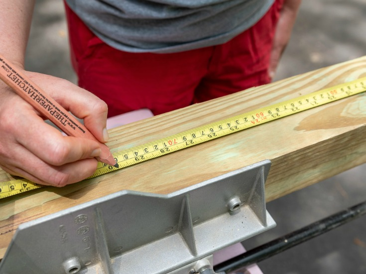 woman measuring wood lumber