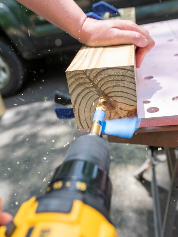 woman drilling hole into wood lumber