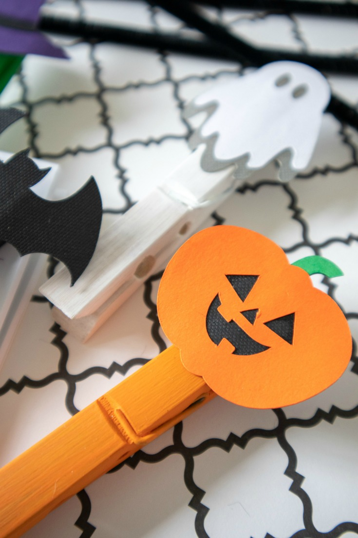 white and orange painted clothespins with halloween die cuts glued on top