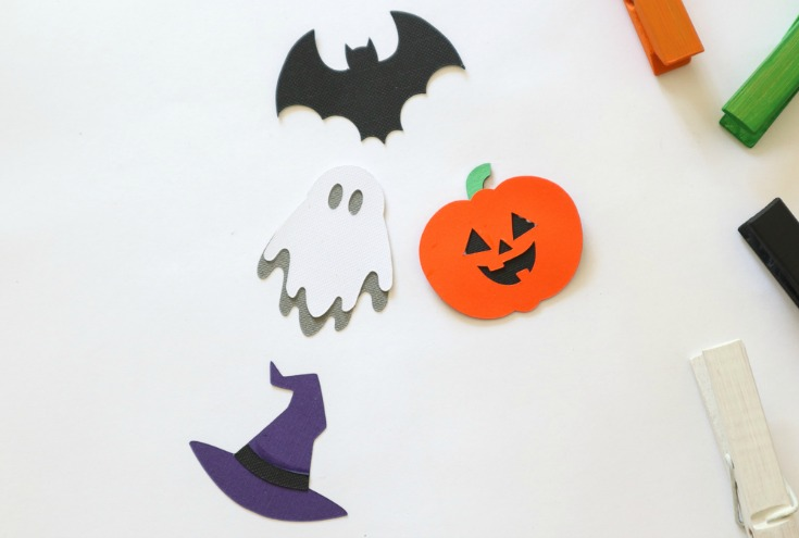 small die cuts in the shape of a pumpkin ghost bat and witch hat