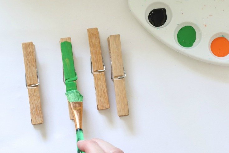 three clothespins with green and black paint