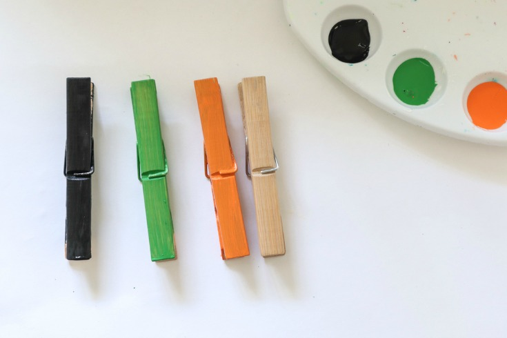 three painted clothespins in green orange and natural