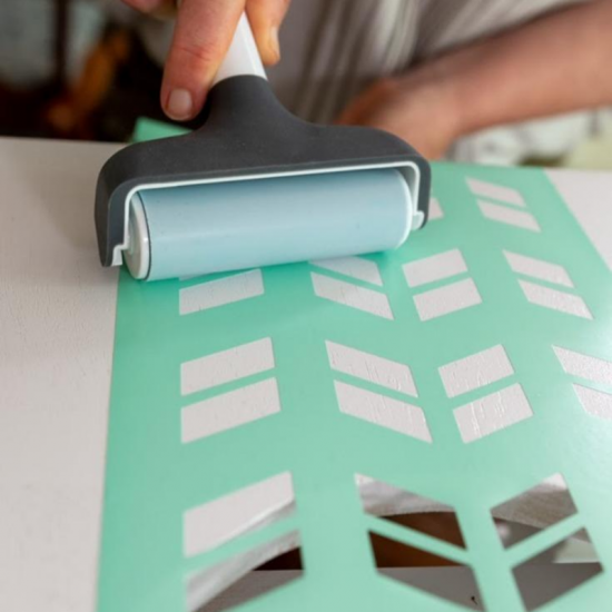 a woman using a brayer to apply a stencil to a table top