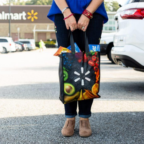 A person standing in a parking lot holding a walmart bag