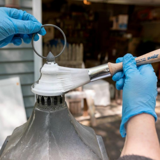 gloved hands adding white paint to a large metal cylinder