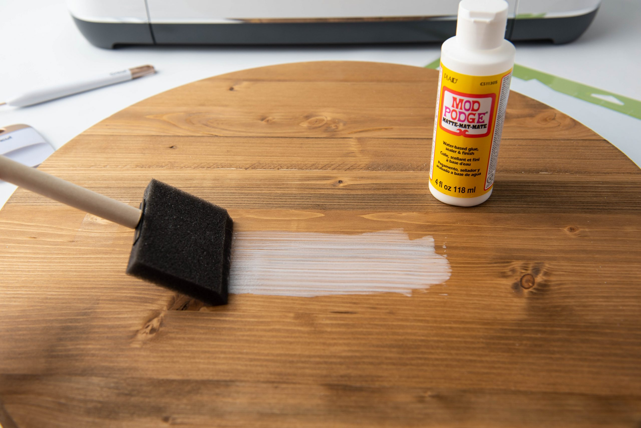 applying mod podge to round piece of wood