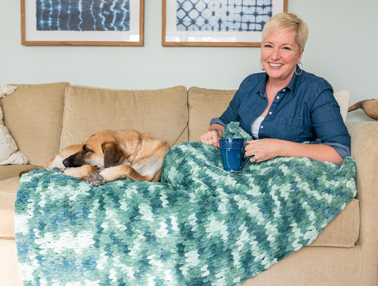 woman sitting on couch with mug, finger knit blanket, and dogs