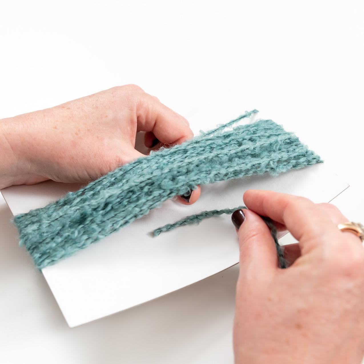 thread piece of yarn underneath the wrapped yarn