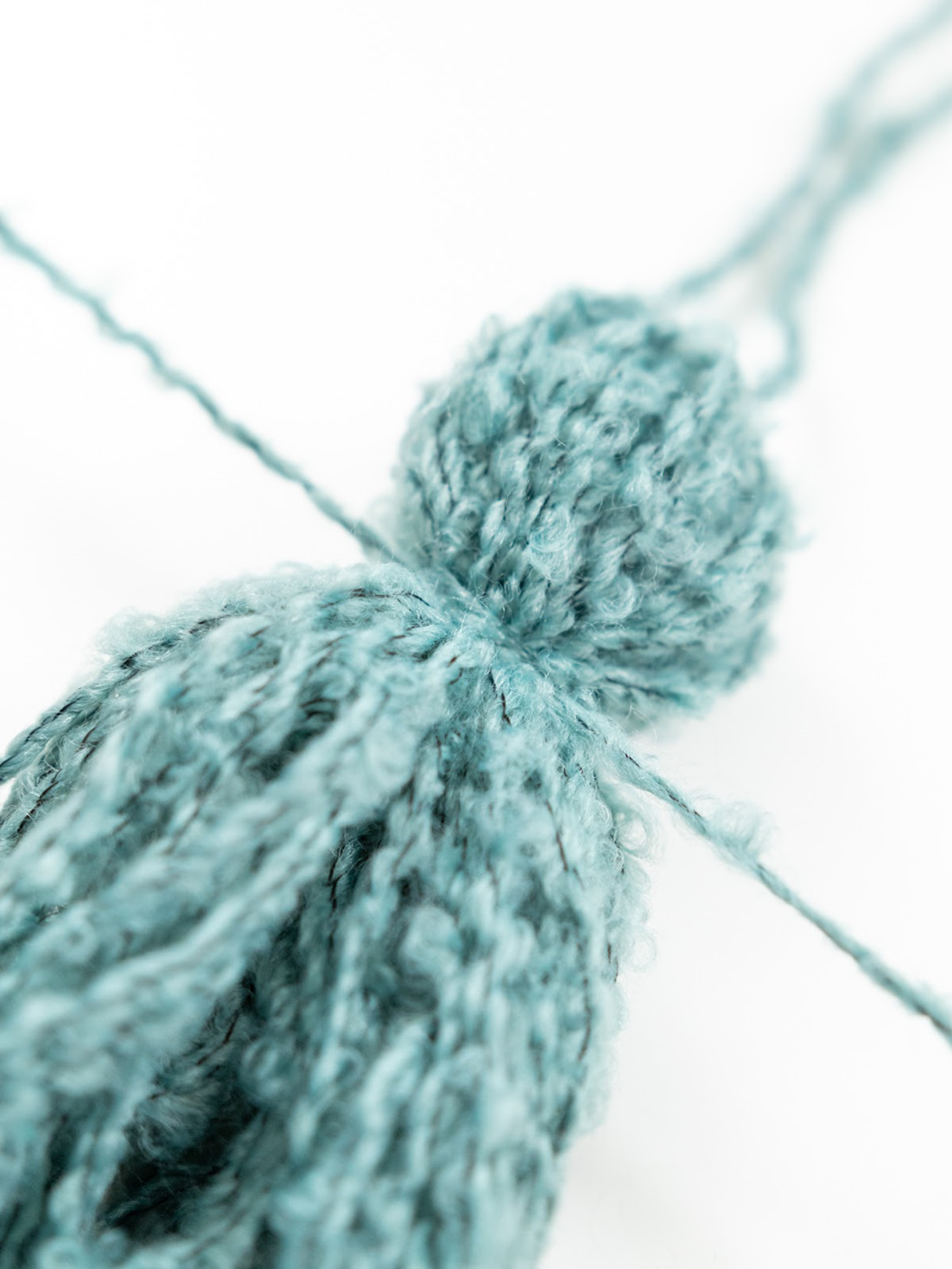 loop piece of yarn around the tassel and tie a knot