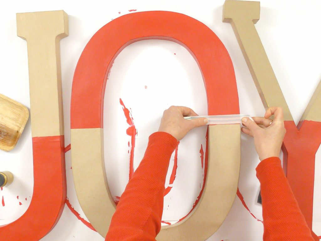 woman tapping off large paper mache letters