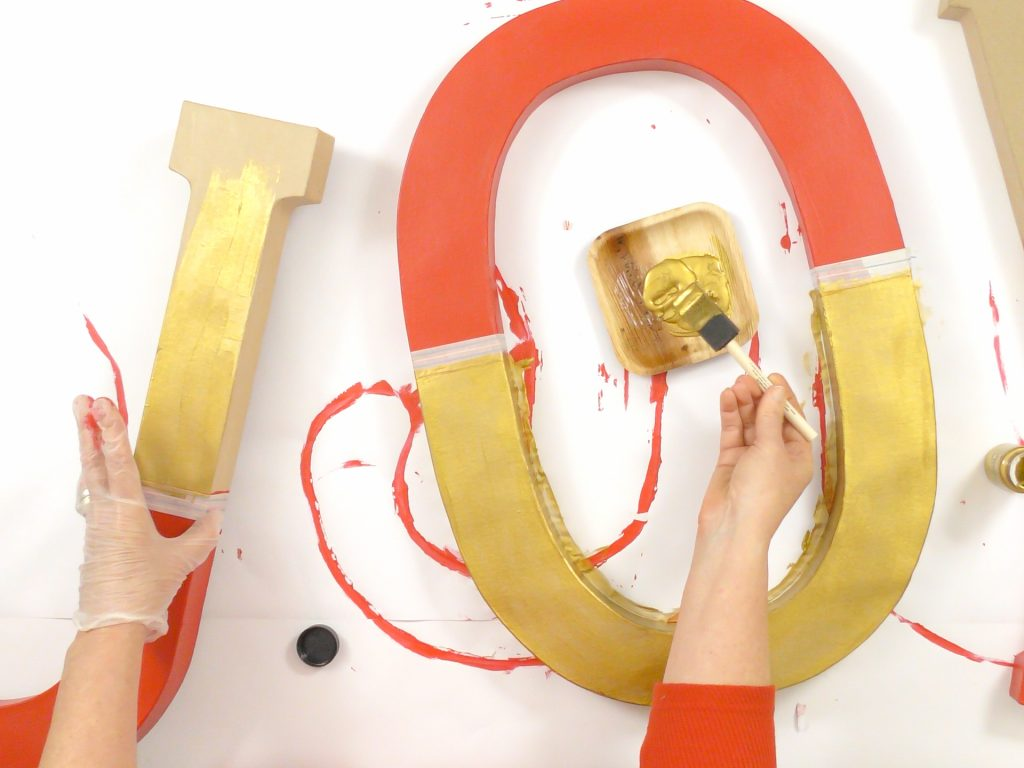 woman using gold paint on joy letters