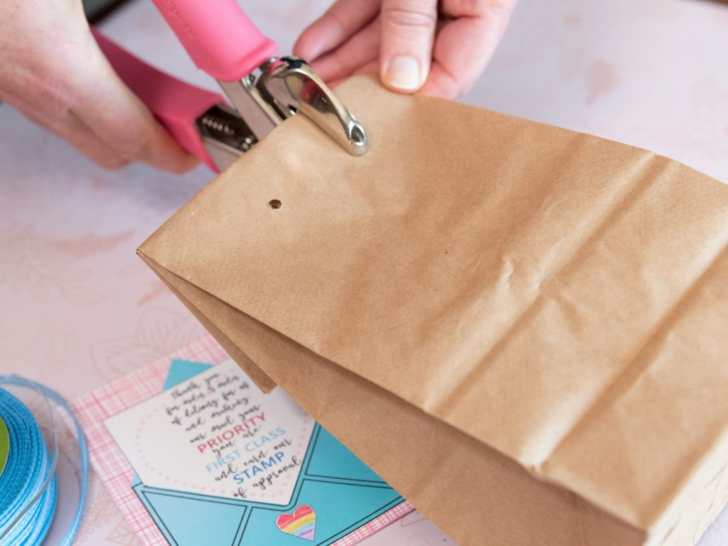 woman using crop-a-dile to punch a hole into a paper bag