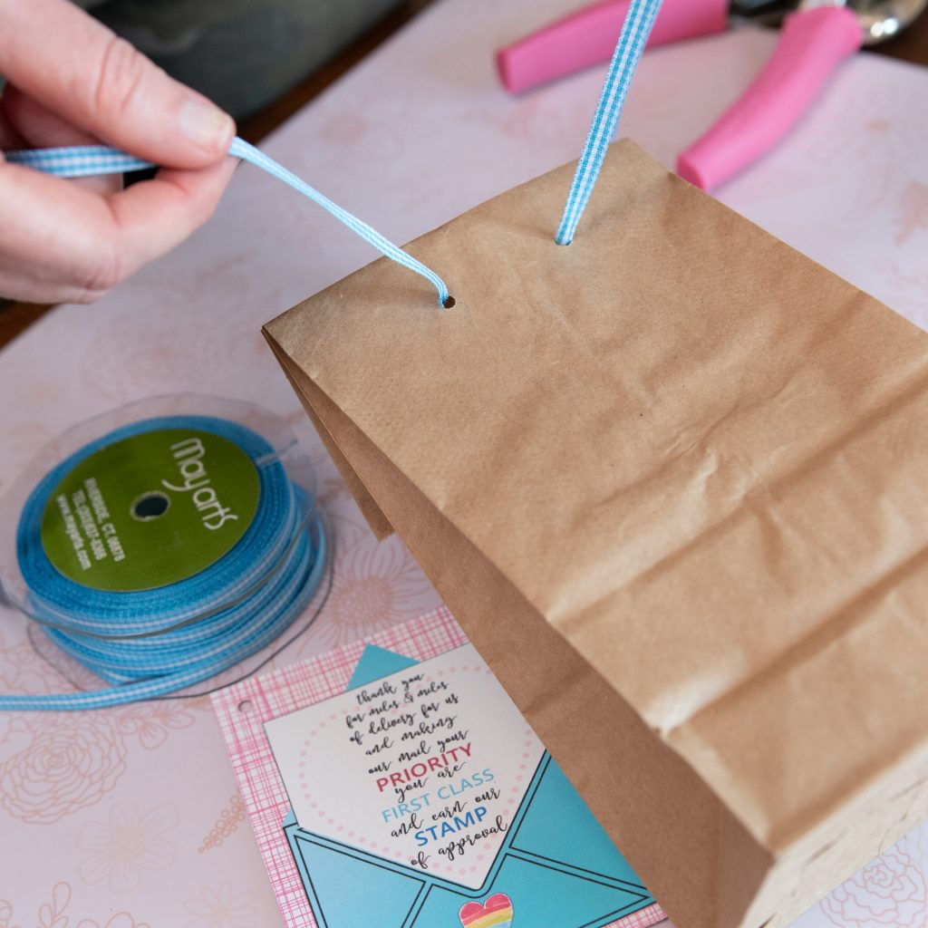 woman adding ribbon on brown paper bag