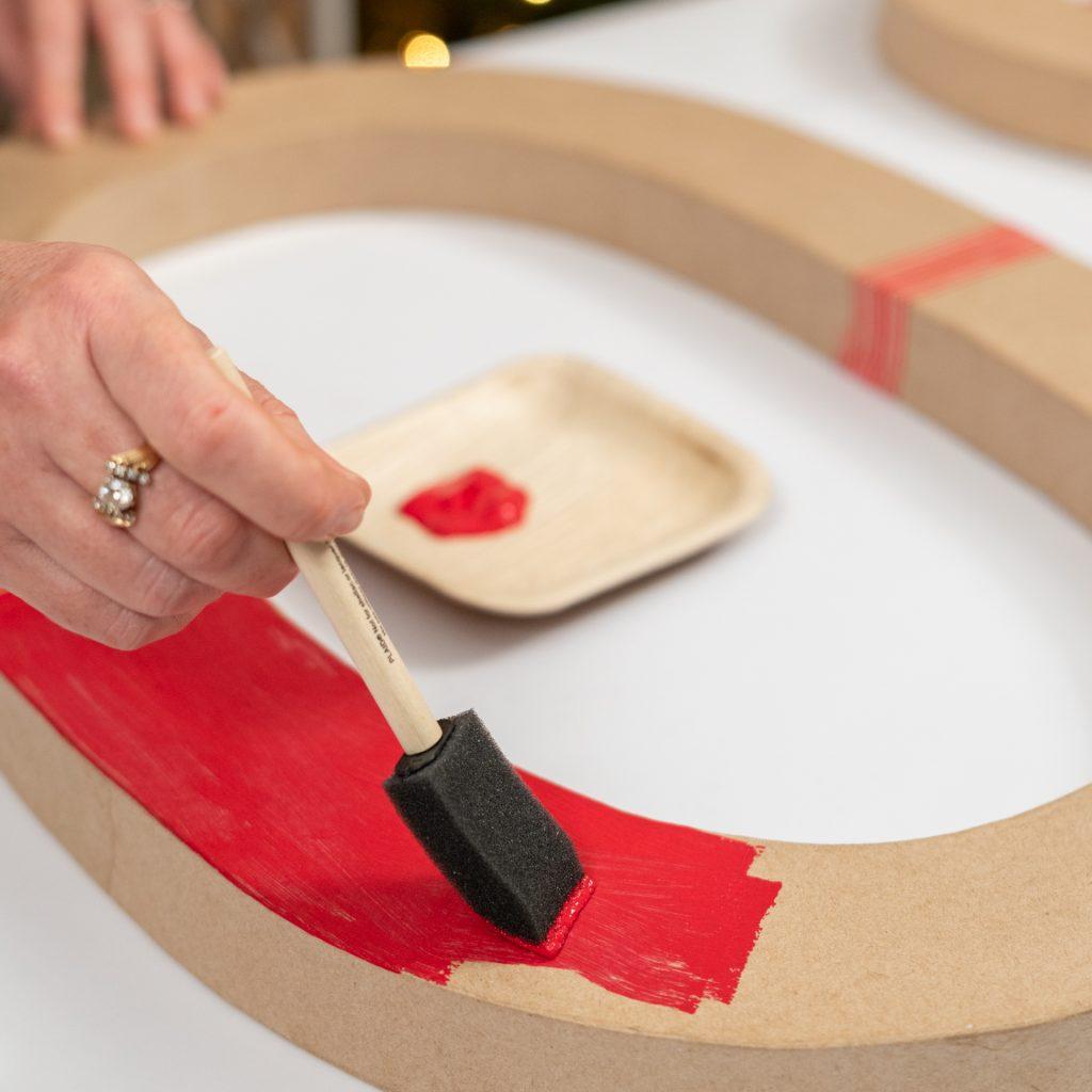 woman painting paper mache letter