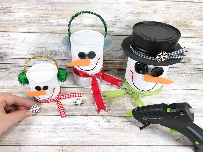 gluing ribbon to snowman soup cans