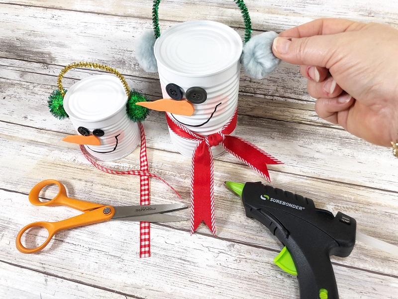hot gluing pom poms to snowman soup cans