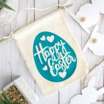 fabric Happy Easter egg banner laying on table next to plants