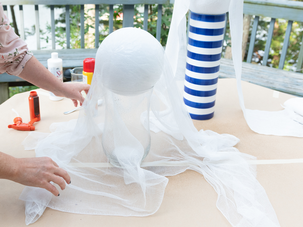 woman covering foam ball with cheesecloth