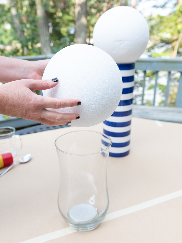 woman holding foam ball over vase
