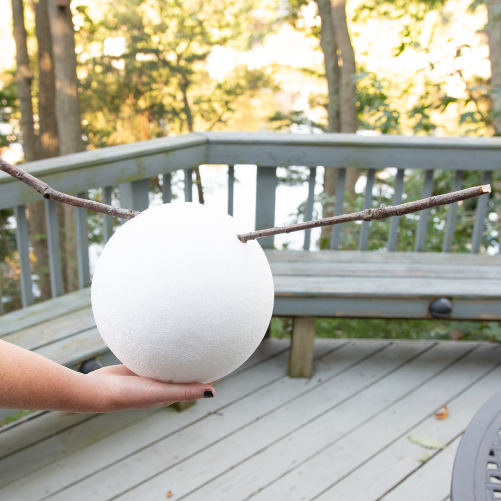 woman holding foam ball with stick arms