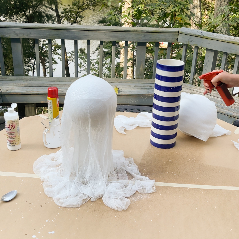 woman spraying Stiffy on cheesecloth ghost